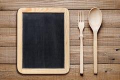 空白的黑板、木叉子和刀子 图库摄影