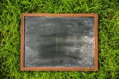 空白的黑板外面在绿草 免版税库存图片