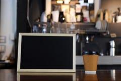 空白的黑板菜单和咖啡在柜台的在咖啡sho 免版税库存照片