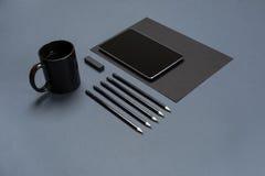 空白的黑纸板料、黑文具项目和咖啡杯平的位置在灰色桌面上 嘲笑 免版税库存照片