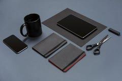 空白的黑纸板料、黑文具项目和咖啡杯平的位置在灰色桌面上 嘲笑 库存照片