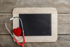 空白的黑板、听诊器和红色心脏,健康背景c 库存照片