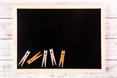 空白的黑板和橙色服装扣子在木桌上 模板 免版税库存图片