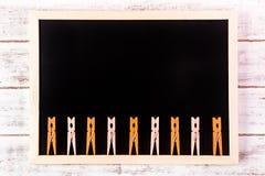 空白的黑板和橙色服装扣子在木桌上 模板 免版税库存照片