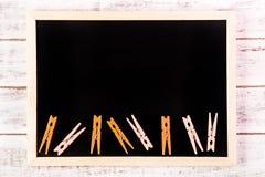 空白的黑板和橙色服装扣子在木桌上 模板 库存图片