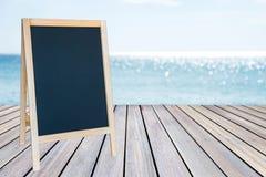 空白的黑板标志和木大阳台与沙子靠岸 免版税库存图片