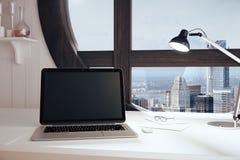 空白的黑膝上型计算机屏幕在有圆的窗口windo的现代屋子里 免版税库存照片
