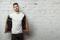 空白的T恤杉的英俊的人脱他的皮夹克,白色砖墙背景的 库存图片