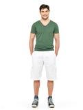 空白短裤和绿色T恤杉的微笑的愉快的人 免版税库存照片
