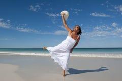 空白礼服的美丽的妇女在海滩 免版税库存照片
