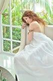 空白礼服的美丽的妇女坐沙发 免版税库存照片