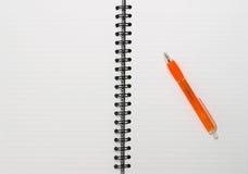 空白空记事本一个橙色笔环形螺旋 免版税库存照片
