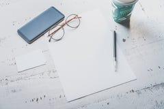 空白纸纸、智能手机、眼睛玻璃和两张空的名片大模型在白色木书桌上 空的事务 免版税库存照片