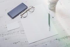 空白纸纸、智能手机、眼睛玻璃和两张空的名片大模型在白色木书桌上 空的事务 库存照片