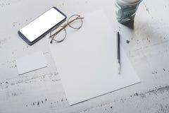 空白纸纸、智能手机、眼睛玻璃和两张空的名片大模型在白色木书桌上 空的事务 免版税库存图片