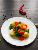 空白背景新鲜的庭院混杂的蔬菜 花椰菜、硬花甘蓝和红萝卜在板材 免版税库存照片