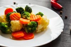 空白背景新鲜的庭院混杂的蔬菜 花椰菜、硬花甘蓝和红萝卜在板材 免版税库存图片