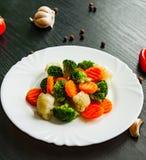 空白背景新鲜的庭院混杂的蔬菜 花椰菜、硬花甘蓝和红萝卜在板材 库存照片