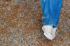 空白蓝色牛仔裤的运动鞋 库存图片