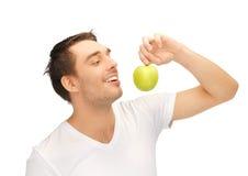 空白衬衣的人用绿色苹果 库存图片