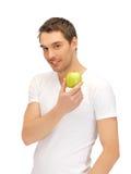 空白衬衣的人用绿色苹果 免版税库存照片