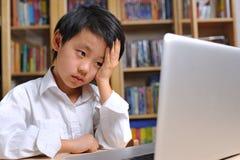 空白衬衣的沮丧的男孩在膝上型计算机前面 免版税库存图片