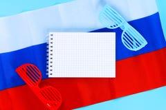 空白记事本 红色和蓝色太阳镜 天6月12日,俄罗斯的 三色俄罗斯的旗子 库存图片