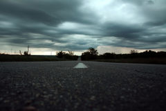 空的乡下路在风雨如磐的天空下 免版税图库摄影
