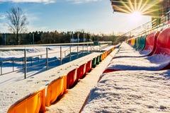 空的五颜六色的橄榄球& x28;Soccer& x29;体育场位子在雪包括的冬天-与太阳火光的晴朗的冬日 库存图片