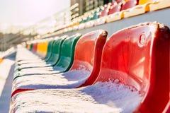 空的五颜六色的橄榄球(Soccer)体育场位子在雪包括的冬天-与太阳火光的晴朗的冬日 库存照片