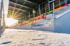 空的五颜六色的橄榄球& x28;Soccer& x29;体育场位子在雪包括的冬天-与太阳火光的晴朗的冬日 库存照片