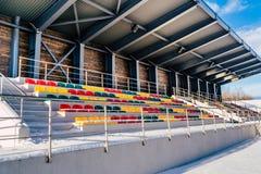空的五颜六色的橄榄球(Soccer)体育场位子在雪包括的冬天-晴朗的冬日 库存图片