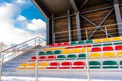 空的五颜六色的橄榄球& x28;Soccer& x29;体育场位子在雪包括的冬天-晴朗的冬日 免版税库存图片
