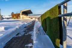 空的五颜六色的橄榄球(Soccer)体育场位子在雪包括的冬天-晴朗的冬日 免版税库存照片