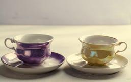 空的五颜六色的瓷碗筷 在淡紫色背景的黄色和紫罗兰色杯子 定调子 图库摄影