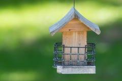 空的使用的板油鸟房子鸟饲养者在后院有绿色背景 免版税图库摄影