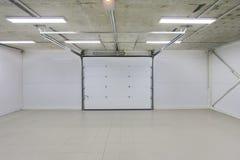空的停车库,储藏与大白色门和灰色砖地的内部 免版税库存照片