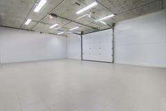 空的停车库,储藏与大白色门和灰色砖地的内部 免版税库存图片
