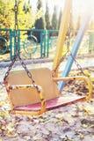 空的儿童` s摇摆在日落的秋天公园 免版税库存照片
