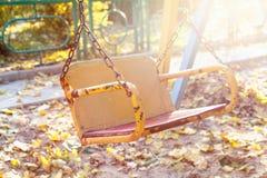 空的儿童` s摇摆在日落的秋天公园 库存照片