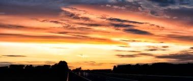空的升起在地平线的柏油路和太阳 在路的五颜六色的日落 最低纲领派样式设计 背景蓝色云彩调遣草绿色本质天空空白小束 库存图片