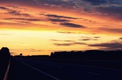 空的升起在地平线的柏油路和太阳 在路的五颜六色的日落 最低纲领派样式设计 背景蓝色云彩调遣草绿色本质天空空白小束 免版税库存照片