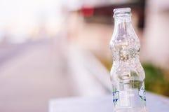 空的可口可乐经典瓶有软的焦点背景 免版税库存图片