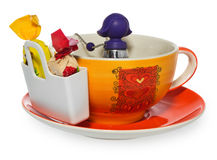 空的咖啡、茶杯有紫色银色infuser的以一个女孩的形式链子的和存贮在糖果与两甜点 杯和 免版税图库摄影