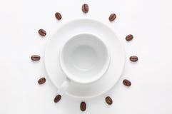 空的咖啡杯和咖啡豆反对形成钟盘的白色背景观看从上面 库存图片