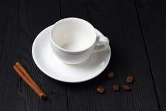 空的咖啡杯用在黑背景的一根肉桂条 库存图片