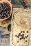 空的咖啡杯用用咖啡豆从上面在肮脏的木头 免版税库存照片