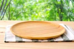 空的圆的木盘子和家庭用亚麻布在桌上在迷离树backg 免版税库存照片