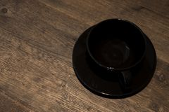 空的在木背景的咖啡黑杯子 库存照片