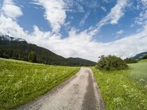 空的地面路在有山和森林的意大利阿尔卑斯背景和多云天空的 白云岩 免版税库存图片